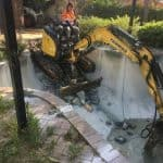 Active Bobcat Services employee removing swimming pool