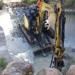 Operater removing a swimming pool with bobcat